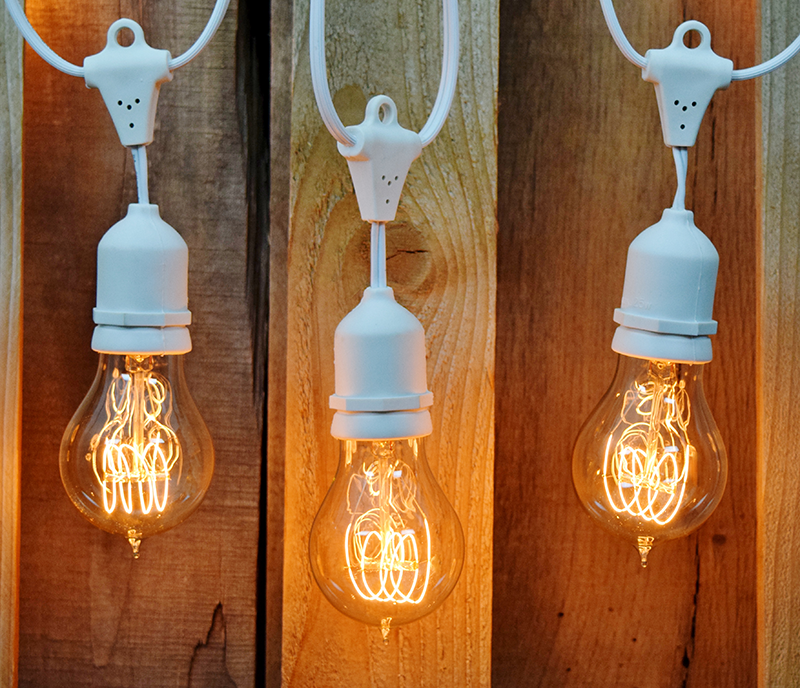 White commercial string lights with antique light bulbs.